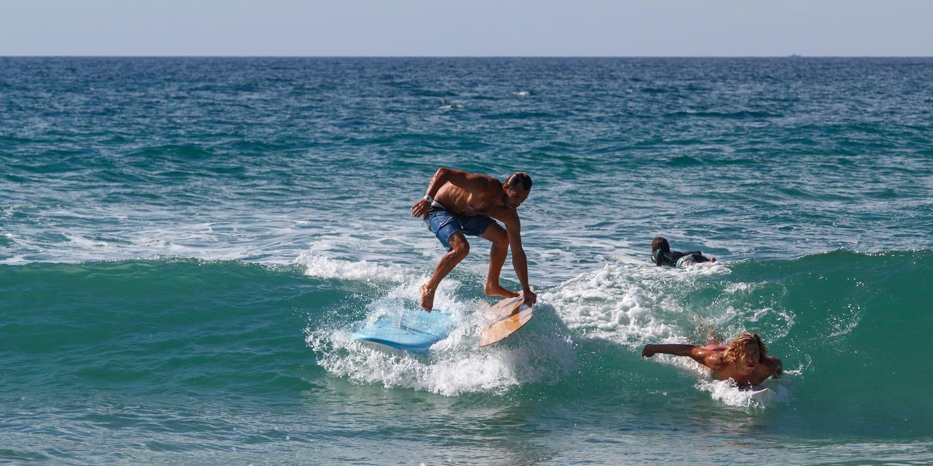 Un surfeur qui saute d'une planche à une autre à Lacanau