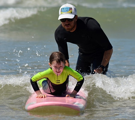 Moniteur de surf poussant une jeune stagiaire sur sa première vague