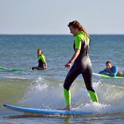 Surfeuse debout sur sa planche sous les yeux de ses amis