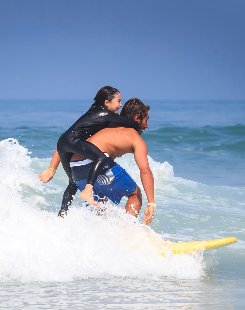 Jeune surfeuse sur les épaules de son moniteur de surf à Lacanau