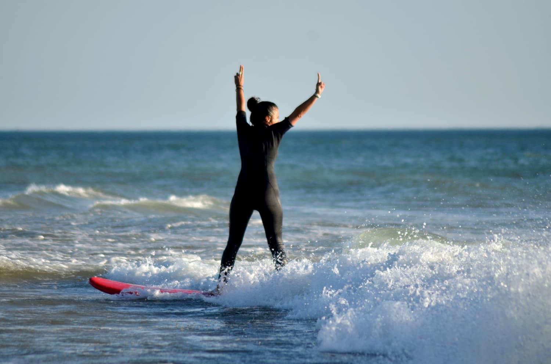 Surfeuse levant les bras de bonheur debout sur sa planche portée par une vague