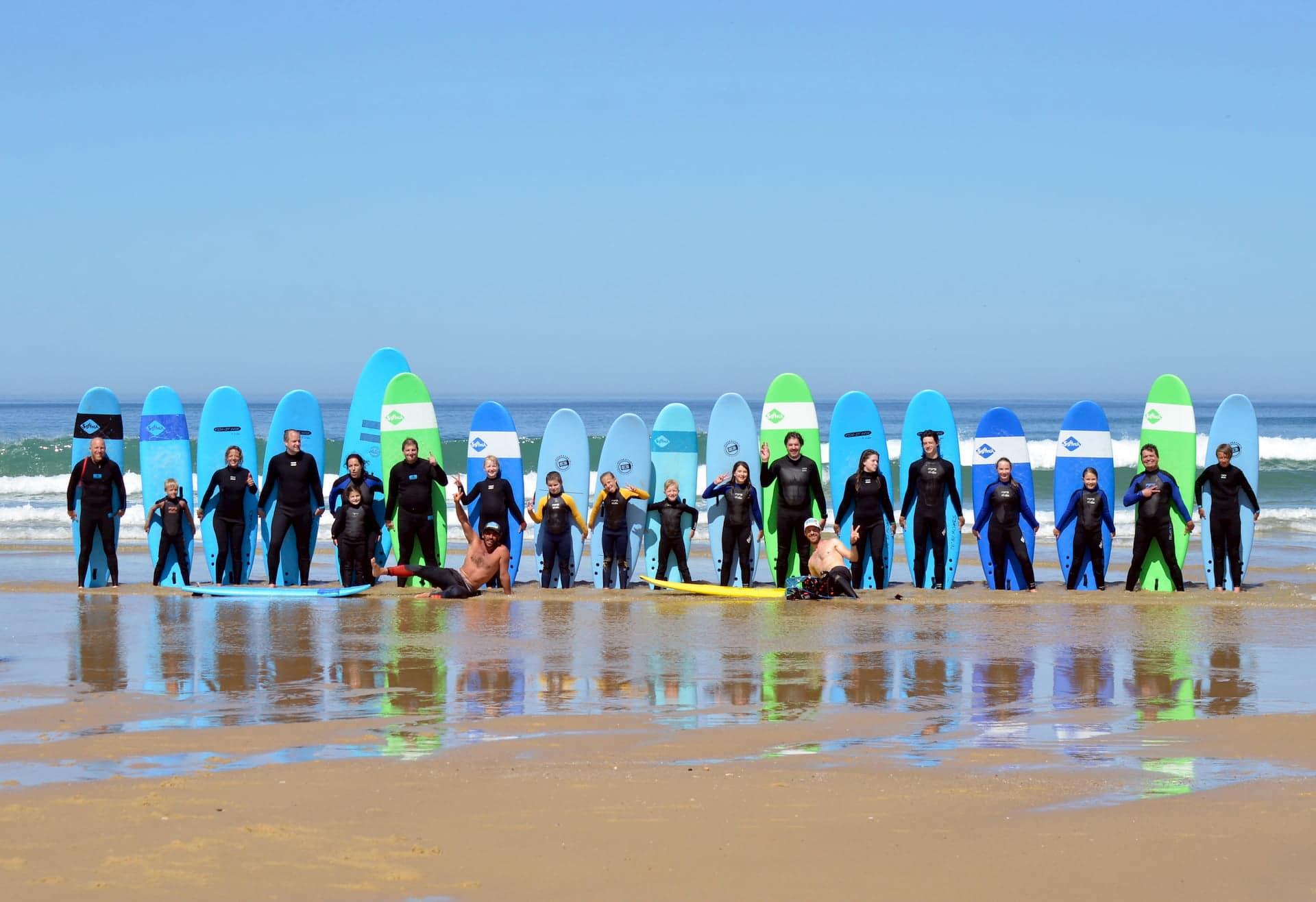 Groupe de surfeurs posant avec leurs planches après une séance d'initiation de surf à Lacanau