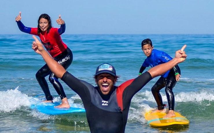 Adrien et ses stagiaires debout sur leurs planches de surf