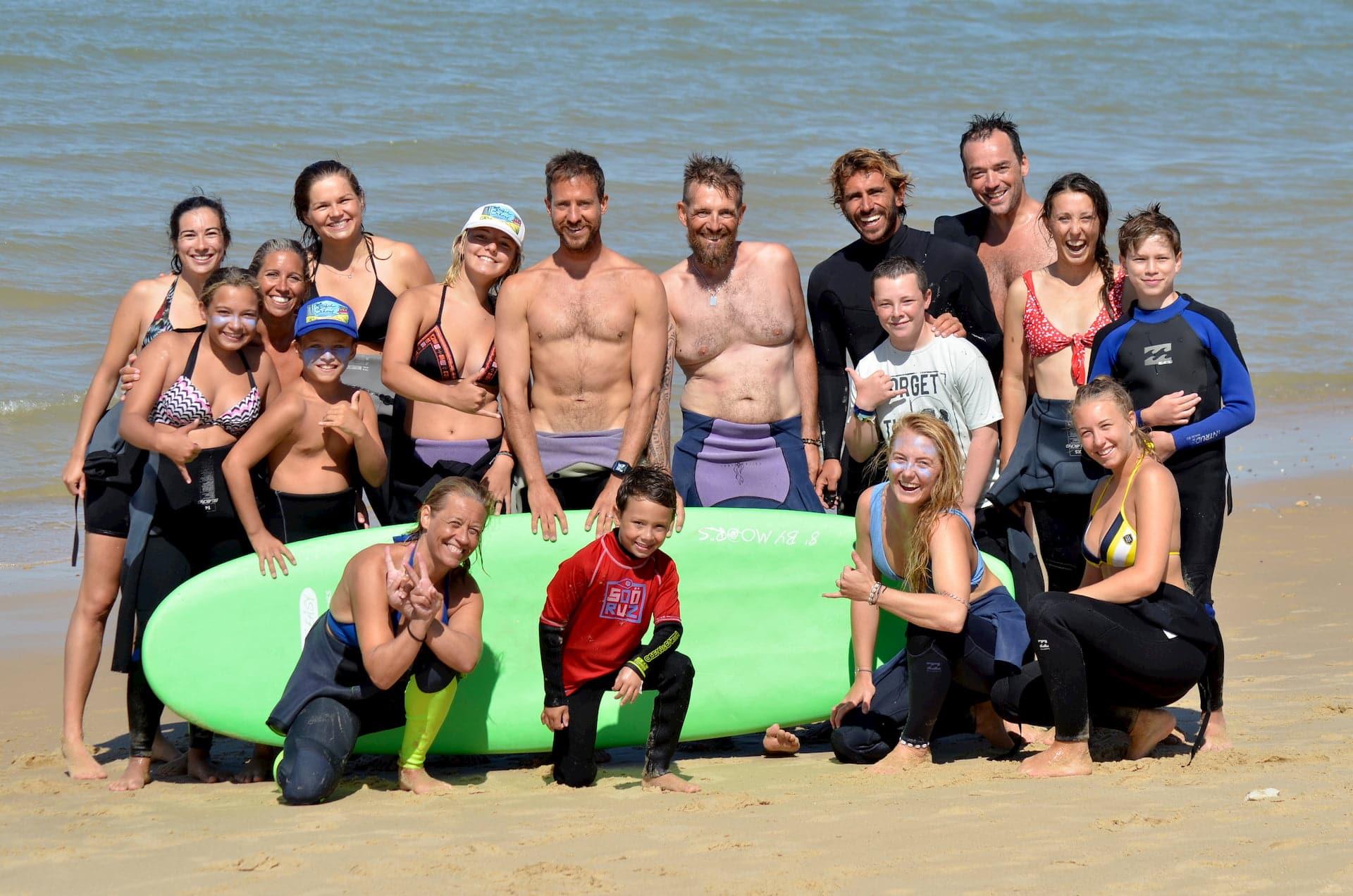 Une famille nombreuse pose sur la plage après un cours de surf collectif ave Magic Surf School Lacanau
