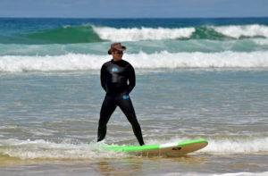 Surfeur prenant la pose debout sur sa planche et portant un chapeau