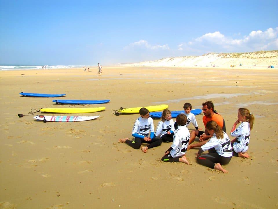 groupe d'enfants sur la plage qui se préparent à aller surfer