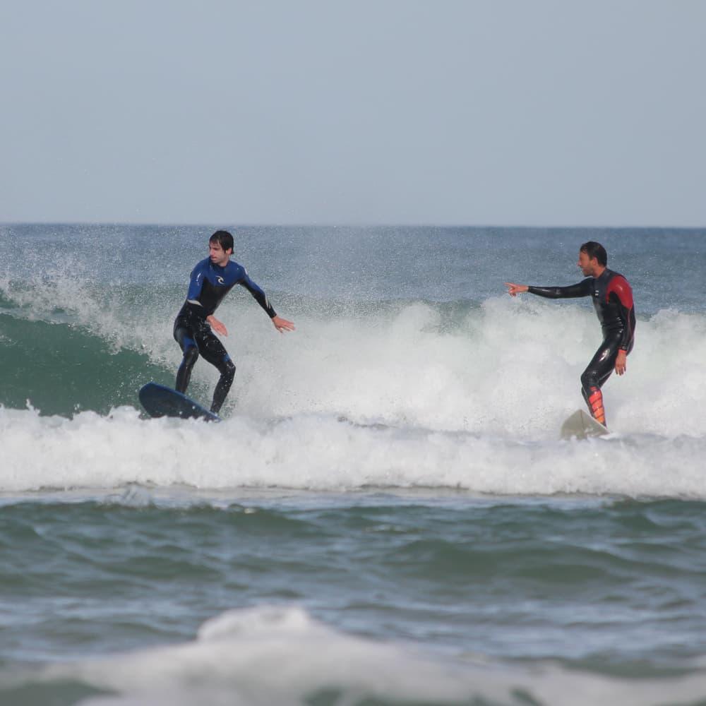 Le moniteur de surf donne des conseils en direct à son élève sur la même vague