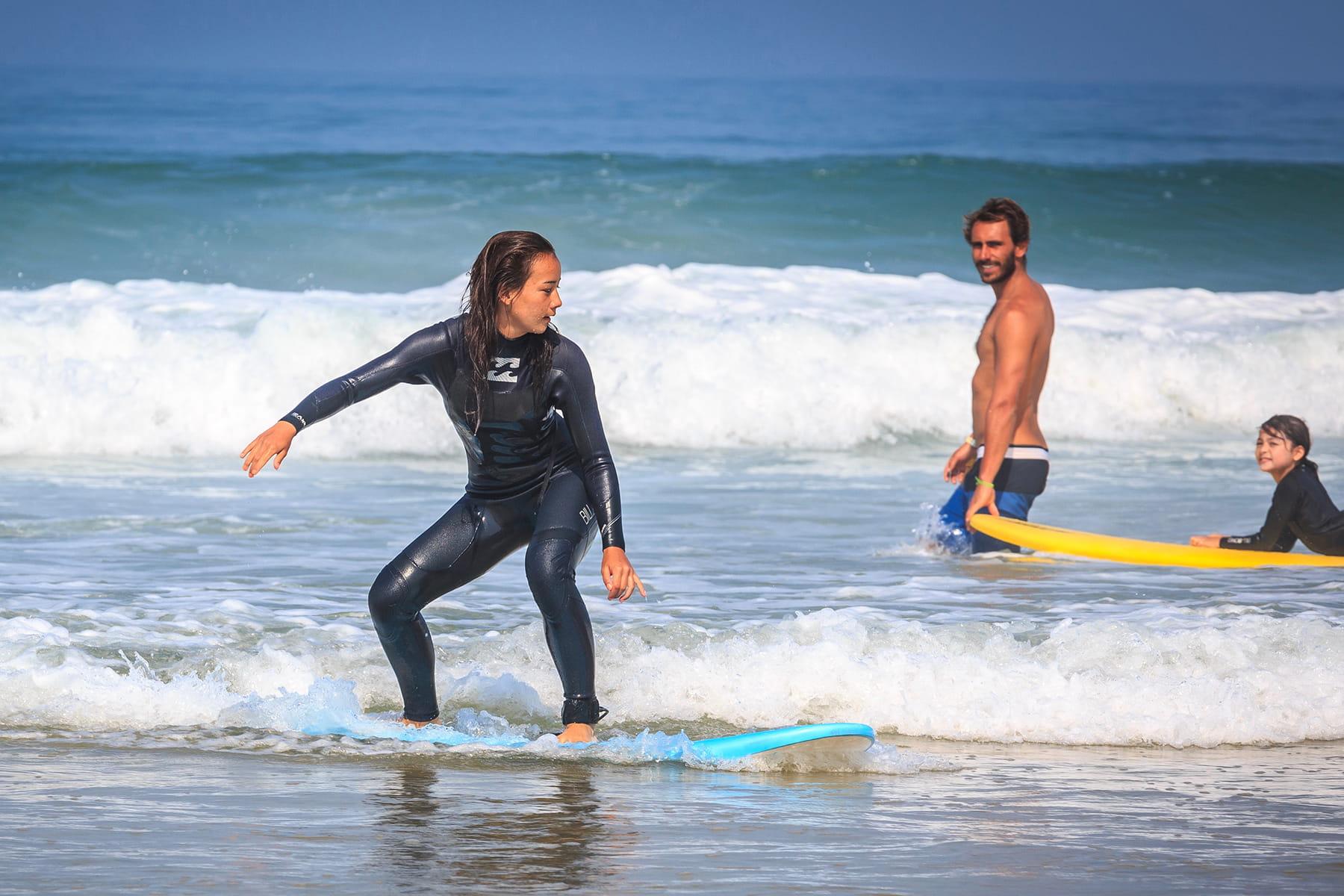 Moniteur de surf observant une de ses stagiaires debout sur sa planche