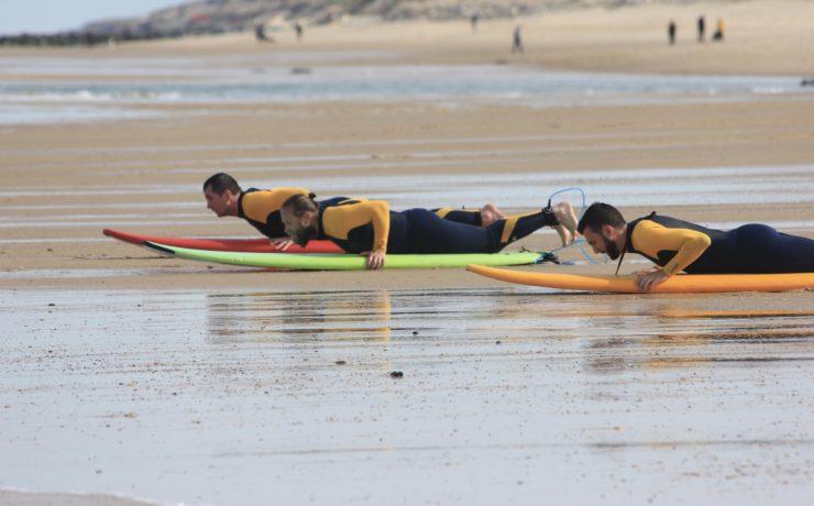trois personnes allongées sur des planches de surf à Lacanau
