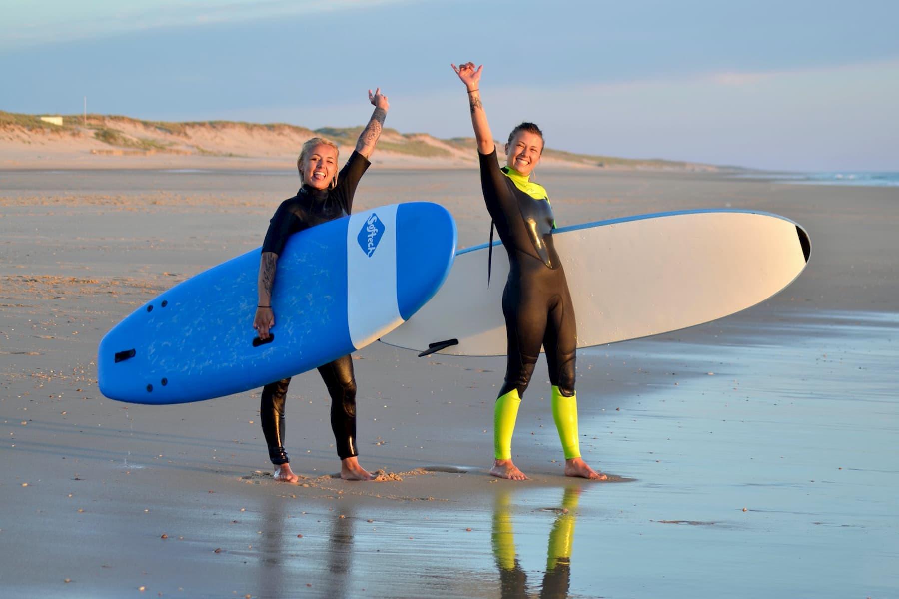 Deux filles qui lèvent les bras après un cours de surf à Lacanau